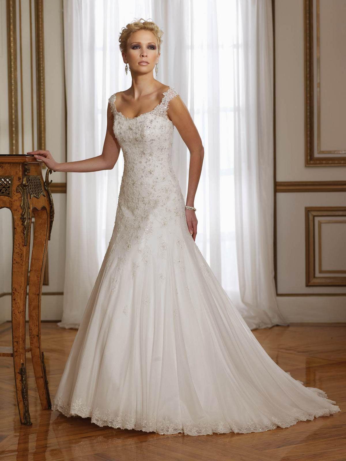 Белое платье на кружевных бретельках расшито сверкающими бусинами. Простой силуэт дополнен пышным подъюбником нужной формы. Небольшой шлейф не сковывает